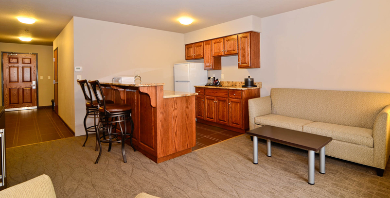 spacious kitchenette with bar stools and a seating area Dickinson, ND